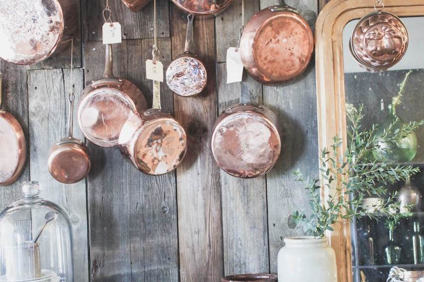 copper pots hanging on old wood wall