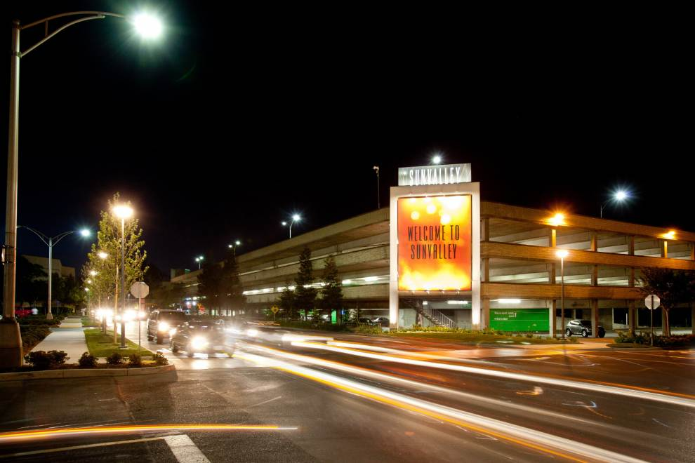 Cars drive past Sunvalley Mall at night